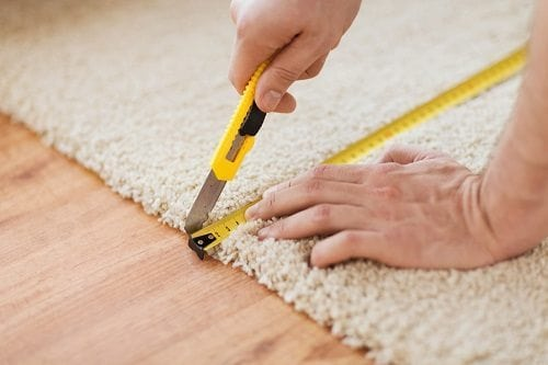 Male hands measuring and cutting carpet with blade