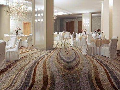 Modern banquet layout using patterned solution dyed nylon carpets with white cloth covered tables and chairs