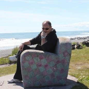Ian sitting on a stone sofa with beach in the background